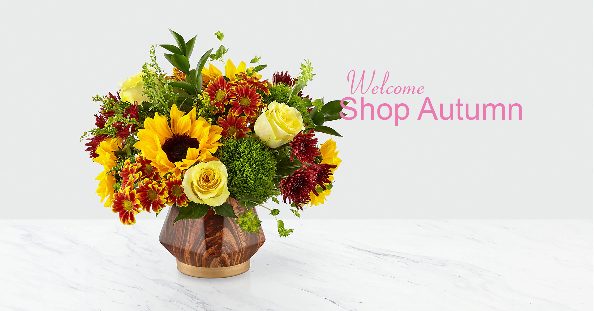 For a limited time our Fall Harvest Bouquet. Set in a striking, wood inspired geometric ceramic vase, this arrangement is comprised of gorgeous yellow roses, sunflowers, green trick dianthus and more.