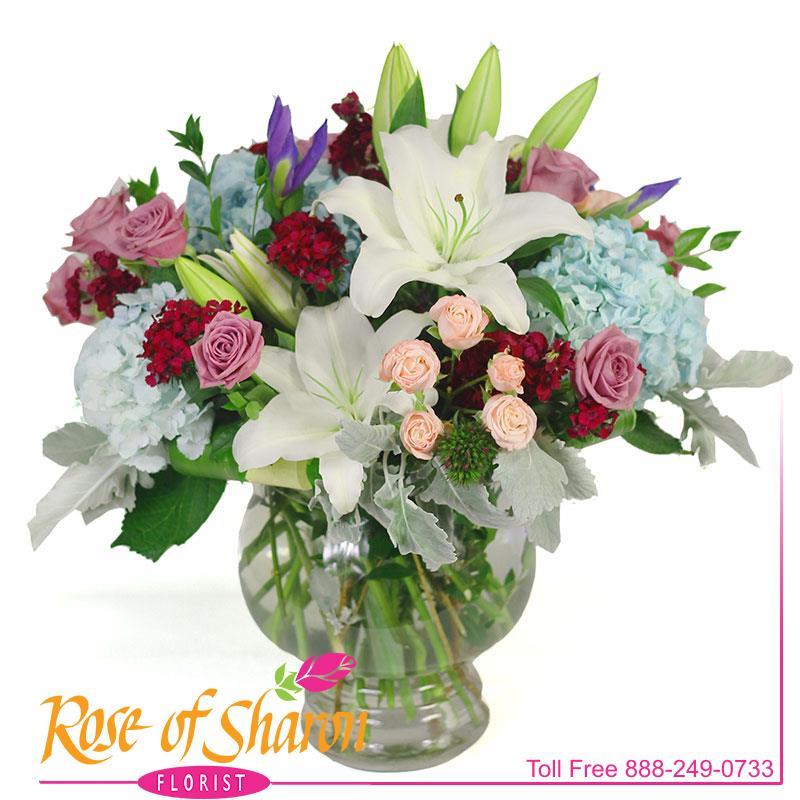 Emily is a large and lovely vase arrangemnent of soft blue hydgrangea, blue iris, fragrant lavender roses and white orchid lilies. Finished with pink spray roses and tufts of dusty miller and sweet william and arrives in a glass urn.