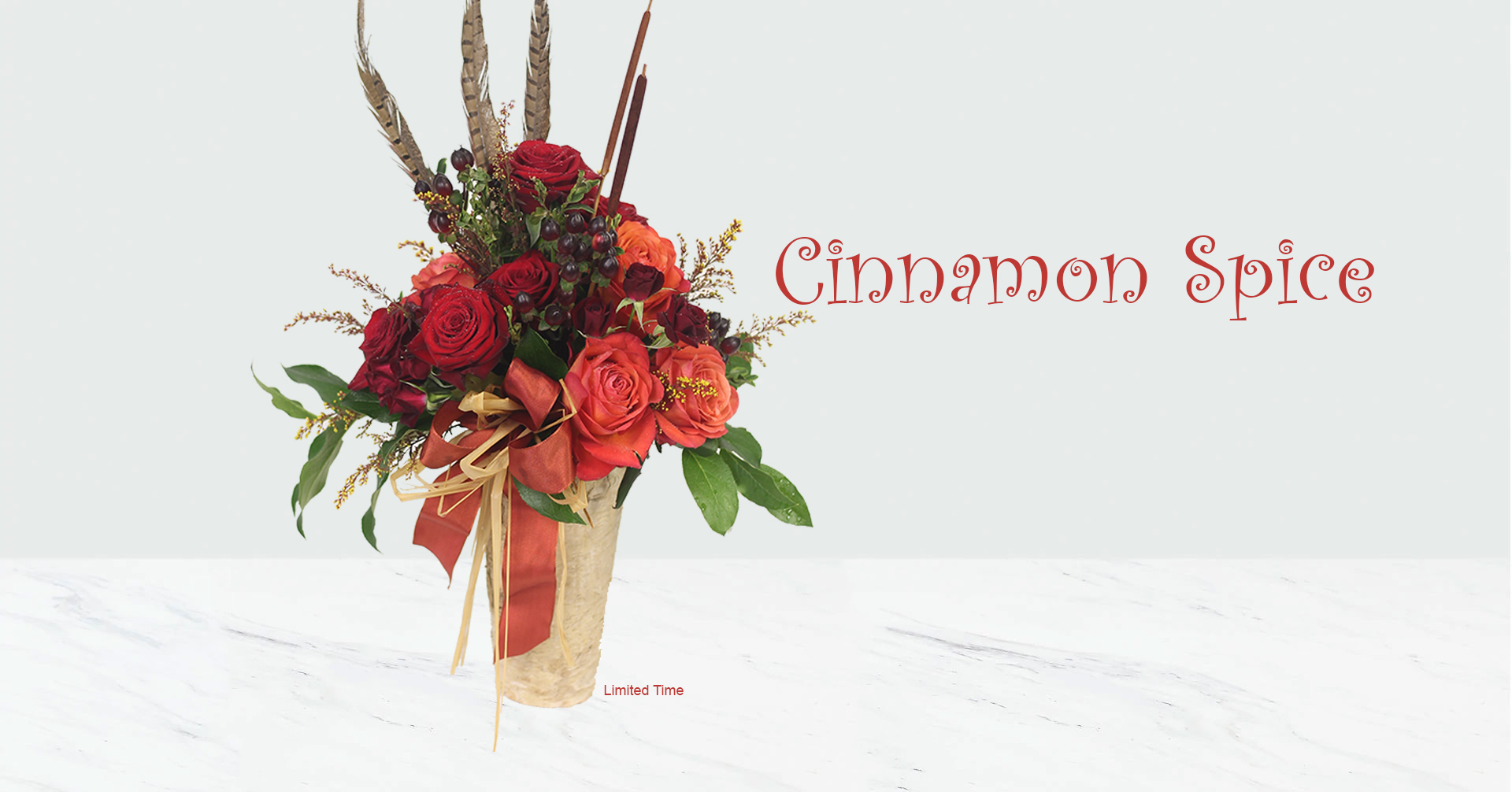 Cinnamon Spice Rose Arrangement, an Autumnal selection of crimson and orange roses and spray roses, cinnamon hypericum and cattails in a birch vase. Finished with pheasant feathers.